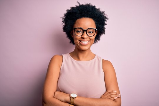 Young beautiful African American afro woman with curly hair wearing t-shirt and glasses happy face smiling with crossed arms looking at the camera. Positive person.