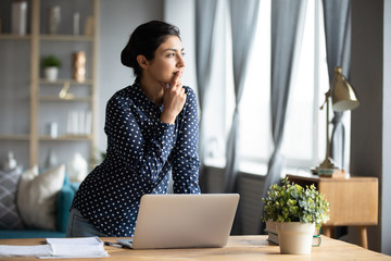 Fototapeta Thoughtful Indian woman standing at desk, businesswoman freelancer pondering difficult task, looking out window, touching chin, pensive young female student working on research project obraz