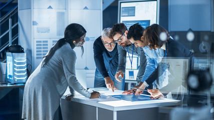 Engineers Meeting in Technology Research Laboratory: Engineers, Scientists and Developers Gathered Around Illuminated Conference Table Talking and Finding Solution, Inspecting Industrial Engine Design
