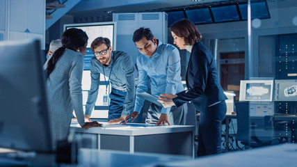 Engineers Meeting in Technology Research Laboratory: Engineers, Scientists and Developers Gathered Around Illuminated Conference Table, Talking and Finding Solution. Industrial Design Facility