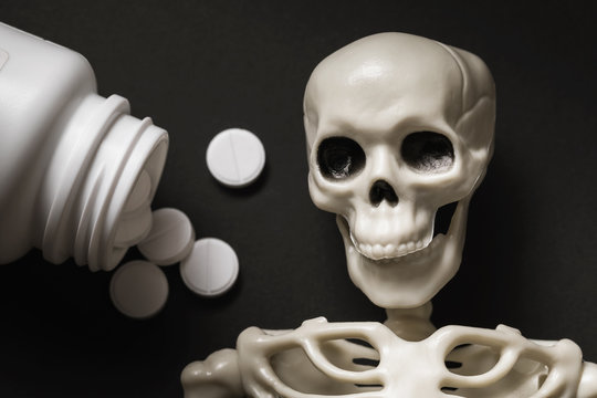 Human skeleton and pills on the table, top view. Poisoning concept