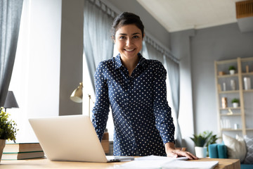 Portrait smiling Indian girl standing at desk with laptop, looking at camera, successful businesswoman freelancer posing for photo at workplace, satisfied excited female student in living room Fotobehang