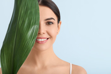 Beautiful young woman with tropical leaf on color background