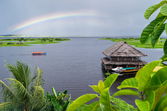 View of the Amazon River tributary in Iquitos, Peru. A rainbow over the river and a beautiful building floating on the water.