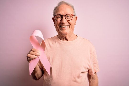 Grey haired senior man holding breast cancer awareness pink ribbon over pink background with a happy face standing and smiling with a confident smile showing teeth