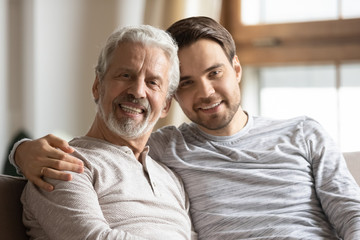 Headshot portrait of happy young man hug cuddle elderly father relaxing at home together, smiling...
