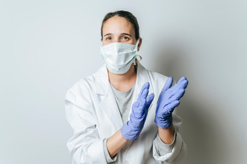 Female doctor with face mask applauding