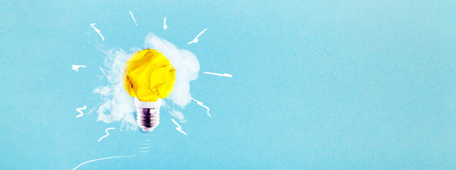 Wall Mural - crumpled yellow paper light bulb on a blue background with smoke, concept idea, panoramic mock-up with space for text