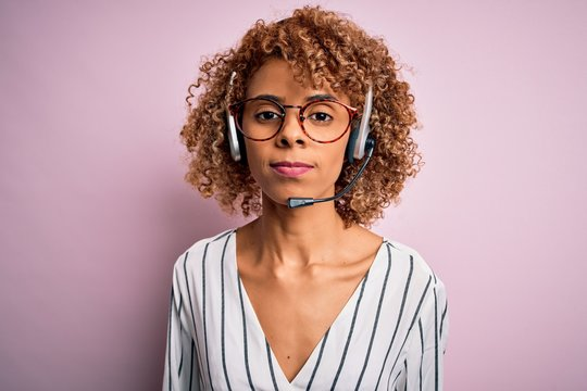 African american curly call center agent woman working using headset over pink background Relaxed with serious expression on face. Simple and natural looking at the camera.