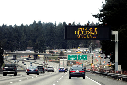 """A sign that reads """"Stay home, limit travel, save lives"""" is pictured on northbound Interstate 5 as efforts continue to help slow the spread of coronavirus disease (COVID-19) in Seattle, Washington"""