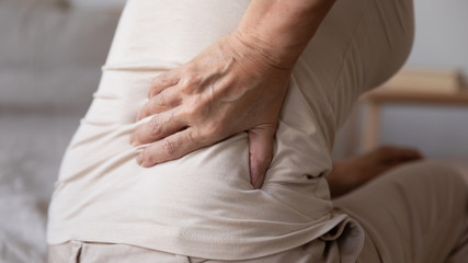 Close up older retired woman sitting on bed, touching lower back, suffer from painful feelings....