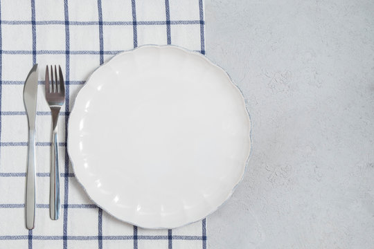 Empty white plate and silverware with napkin on neutral table background