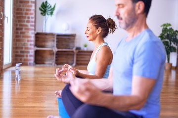 Middle age beautiful sporty couple sitting on mat practicing yoga doing lotus pose at gym