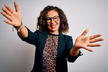 Wall Mural - Middle age brunette business woman wearing glasses standing over isolated white background looking at the camera smiling with open arms for hug. Cheerful expression embracing happiness.