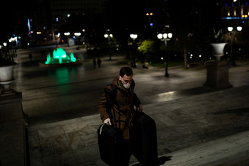 A man wearing a protective face mask and gloves carries his luggage on Syntagma square, during an outbreak of the coronavirus disease (COVID-19), in Athens