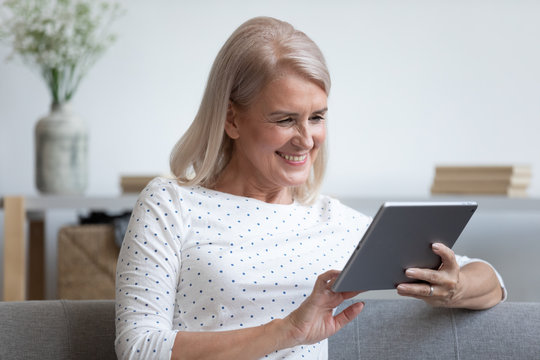 Head shot happy older lady relaxing on comfortable sofa, holding computer tablet in hands, watching movie. Smiling middle aged woman reading book online or making purchases in internet store at home.