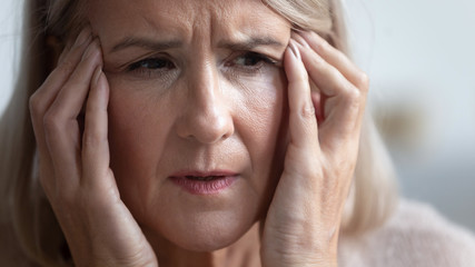 Close up head shot portrait unhealthy mature retired woman massaging temples, suffering from strong sudden headache. Unhappy middle aged woman having high blood pressure, healthcare concept. Wall mural