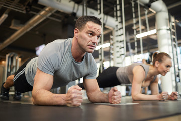 Full length portrait of mature muscular man doing plank exercises during couple workout in modern...