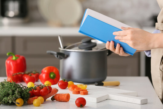 Woman with cook book preparing food in kitchen