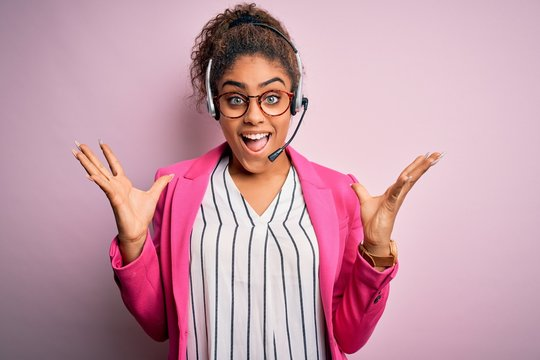 Young african american call center agent girl wearing glasses working using headset celebrating crazy and amazed for success with arms raised and open eyes screaming excited. Winner concept