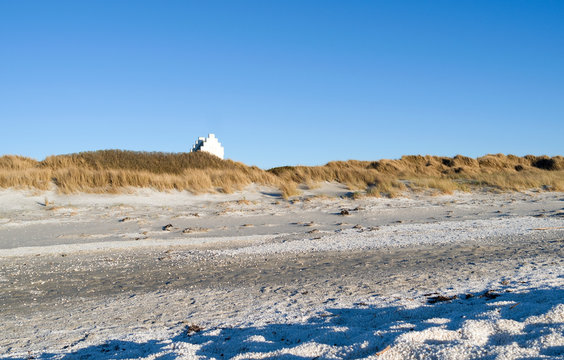 Laesoe / Denmark: View from the beach in Vesteroe Havn over the dunes to the old steeple which is the landmark of Laesoe Kur today