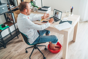 Comic modern home office situation. Businessman have a video call chatting on laptop and soaring his feet in Foot hot Bath under table. Distance work in worldwide quarantine time concept image