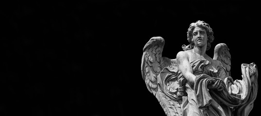 Angel statue holding the garment and dice of Jesus Passion. A 17th century baroque masterpiece at the top of Sant'Angelo Bridge in the center of Rome (Black and White with copy space)