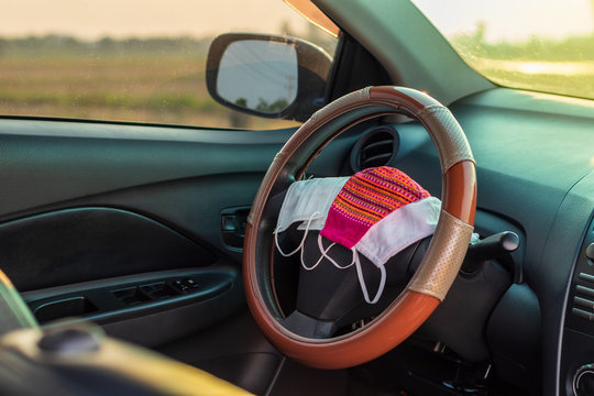 Many face masks are placed on the steering wheel inside the car.