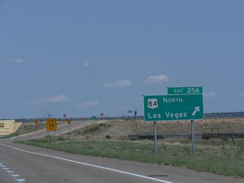 Directional sign on the road with directions to the exit for Las Vegas, New Mexico.