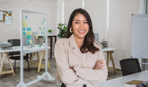 Portrait of Asian Business woman with Arms Crossed and standing at modern workplace, human resource and small business owner, hiring new employee, business person concept.