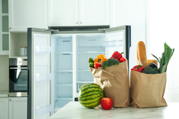 Paper bags with fresh products on table near modern refrigerator in kitchen