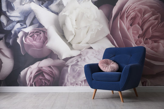 Comfortable armchair near wall with floral wallpaper, space for text. Stylish living room interior