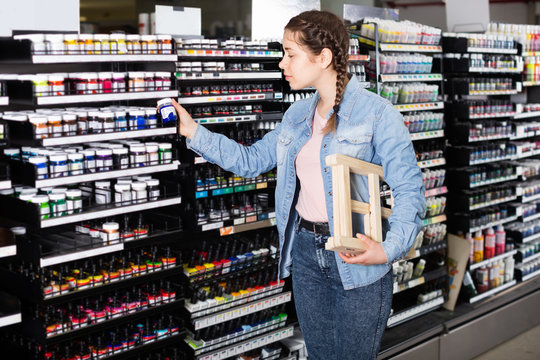 Girl shopping color in glass jar in art store