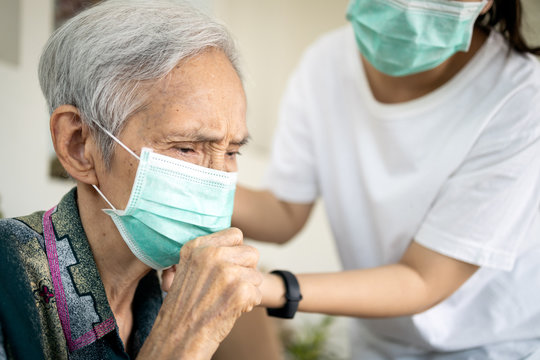 Sick elderly woman with coughing and fever,risk symptoms of flu,pandemic of Covid-19, asian daughter wearing protective mask to senior mother,prevent outbreak or spread of Coronavirus to other people