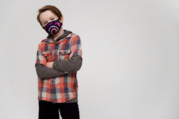 portrait of a teenager boy in a mask in a plaid shirt on a white background