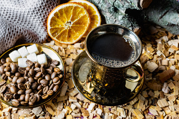 Canvas Prints Cafe Aromatic dark coffee with bubbles on the surface in a dark gold Cup on a saucer, next to whole grains, peeled and dried oranges. Background of alder chips and in the background snags of wood with bark