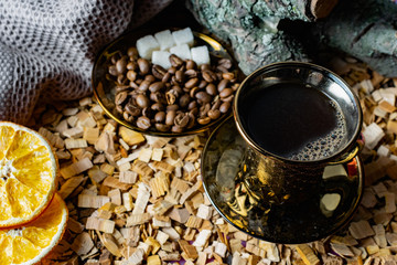 Printed roller blinds Cafe Aromatic dark coffee with bubbles on the surface in a dark gold Cup on a saucer, next to whole grains, peeled and dried oranges. Background of alder chips and in the background snags of wood with bark
