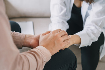 Close-up of psychiatrist hands together holding palm of her patient.  Psychological male comforting and holding a woman hand while sitting on the sofa. psychologist concept