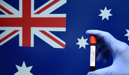 Corona virus or Covid-19 in Australia , sample blood tube in hand with Australia flag on background