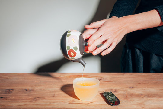 female hands holding a teapot and pouring tea on a cup on wood table