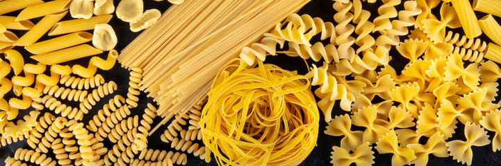 Italian pasta panoramic banner, a flat lay of many different pasta types, shot from the top on a black background