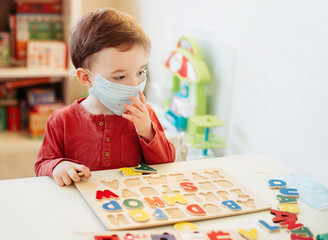 Little boy in medical mask playing letters. He coined the word coronovirus.