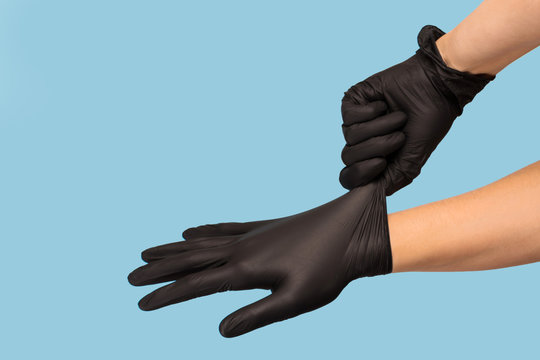man puts on sterile black gloves on a blue background. Hazard, hygiene, control