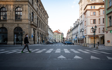 Prague, Czech republic - March 17, 2020: Man with the mask is walking in the historical centre in Prague after coronavirus pandemic. Prague street empty due to coronavirus. Almost deserted