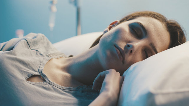 Young woman lying in a hospital bed at night