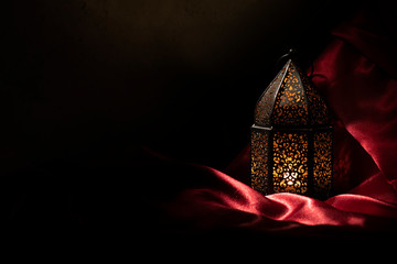 Dark photography of lantern with a dim lighting effect on a red satin cloth.