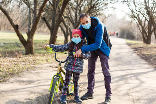 7 years old happy Little hild rides bicycle in the park at home and wearing protection mask for protect pm2.5 and Coronavirus Covid-19 Pandemic virus symptoms. Sport exercise for health.