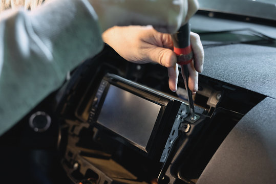 Auto technician is installing a new car radio player close up.