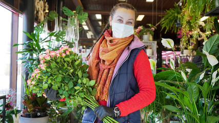 Florist employee in surgical mask protecting herself against COVID-19 coronavirus. Florist female looking into camera.  Fotobehang