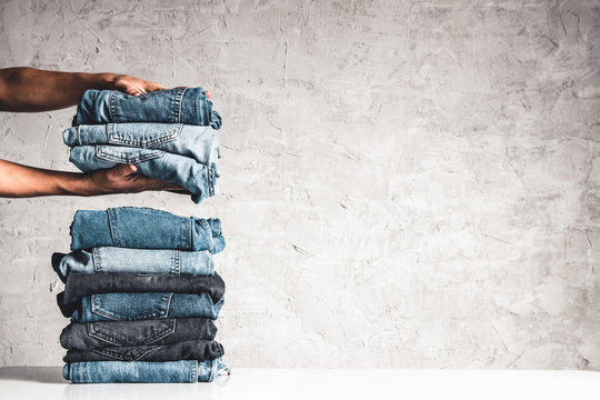 Hands, put the stack of blue jeans on gray background.